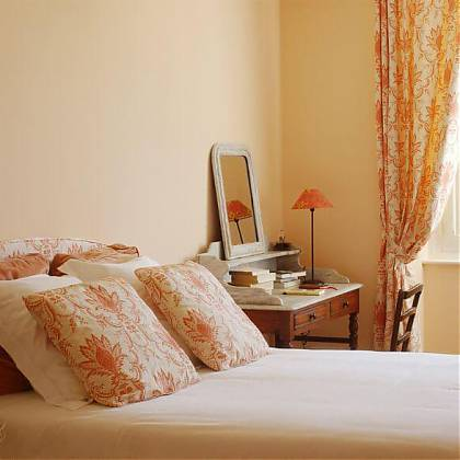 Bedroom with double bed, peach walls, pillows and curtains, dressing table with marble top and mirror.
