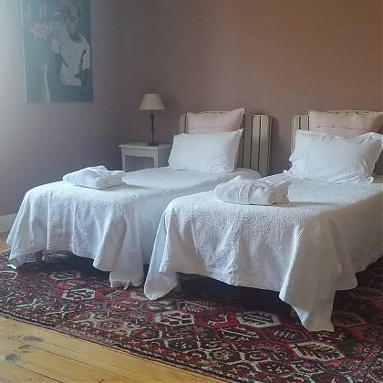 Bedroom with pink walls, two single beds with white covers, dressing table with chair and window.