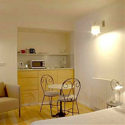 Camelia studio accommodation with bed, kitchenette table and chairs.