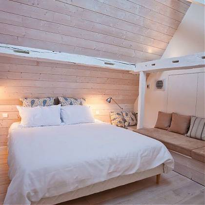 Bedroom with double bed, white bedlinen, wooden panels on walls and floors, seating area on right side.