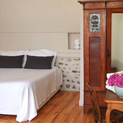 Double bed, white bedcover with two grey pillows. Wooden wardrobe with mirror, pink flowers and towels on table.