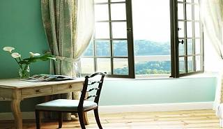 Bedroom with open window, blue walls, blue and white floral curtains, desk with flowers and magazine.