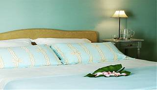 Bedroom with double bed, blue walls, blue and white bedcovers, side table with bedside lamp.