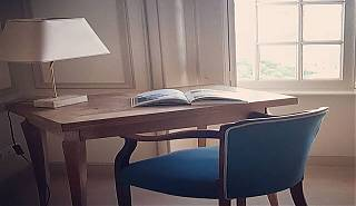 Desk with cream lamp and book. Blue chair and window.