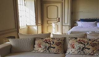 Bedroom detail, beige sofa with floral cushions, window, door and bed.