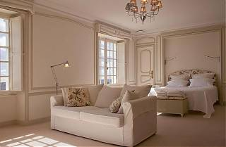 Large bedroom with white walls, carpet, sofa and double bed.