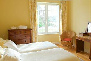 Bedroom with twin beds, yellow walls, yellow floral curtains, wooden drawers and table.