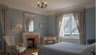 Bedroom with double bed, desk, fireplace, lamp and armchair.