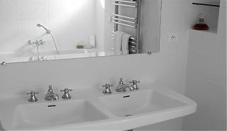 Double sink with mirror, white tiles and towel rail.