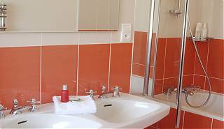 Bathroom with double sink, mirror, peach colour tiles, bath with shower.