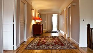 Wide corridor in manor house leading to guest bedrooms. Grey walls, two red and cream rugs, cabinet with orange lamps.