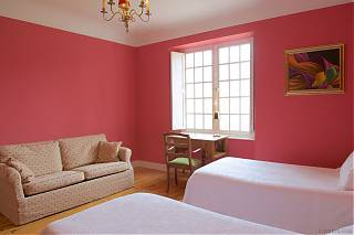 Bedroom with pink walls, beige sofa, dressing table and two single beds.