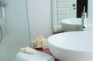 White wash basin, with silver tap, towel with soap and shell to the left.