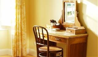 Dressing table with mirror and chair, yellow walls and curtain.