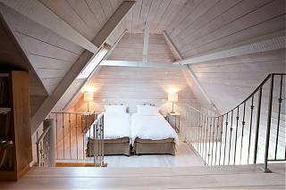 Bedroom with high ceiling in loft apartment. Two single beds with bedside tables and lamps.