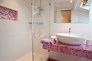 Bathroom with mirror, white hand basin, pink tiles and shower.