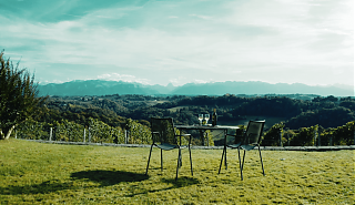 Metal table and two metal chairs on lawn. Two wine glasses and bottle of wine on table. Pyrenees mountains in background.