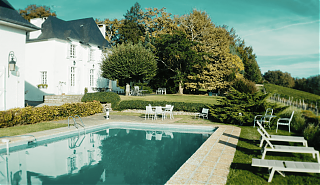 Swimming pool with terrace, tables and chairs. White manor house with black roof.